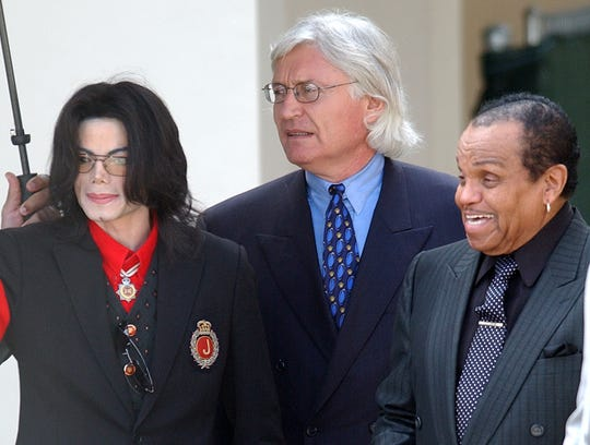 Michael Jackson exits the Santa Barbara County Courthouse, March 24, 2005 with his father, Joe Jackson, right, and his attorney, Thomas Mesereau, during his trial on charges of child molestation. He was ultimately acquitted.