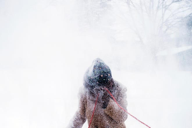 Wind pushes snow back onto Sarah Allen as she clears her driveway with a snowblower Jan. 28, 2019, in Flint. Mich.