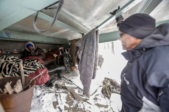 On the eve of the Polar Vortex, Detroit Rescue Mission Ministries Facilities Supervisor Herbert Morris talks with Curtis Farr-El, 58, about seeking shelter at his makeshift home under a viaduct on Interstate 75 in Detroit on Tuesday, Jan. 29, 2019. Some areas of Lower Michigan could face wind chills as low as 45 degrees below zero, according to the National Weather Service.