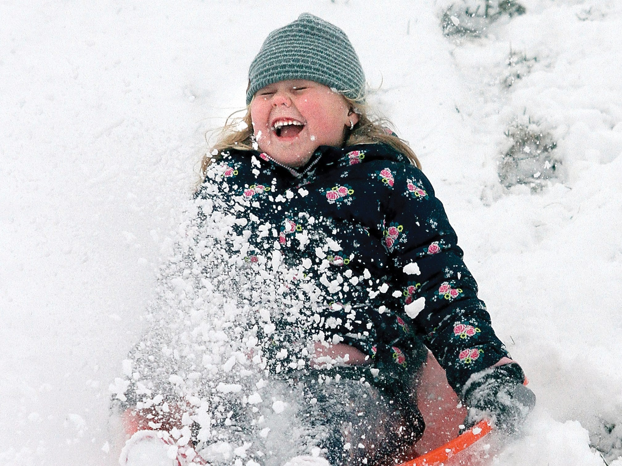 Aralin Jones laughs as she sleds down a hill at Foothills Mall as up to three inches of snow fell Jan. 29, 2019, in Blount County, Tenn, giving students the day out of classes.