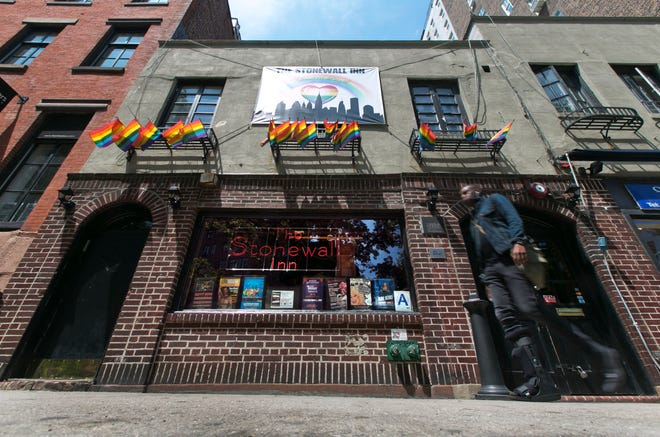 A man passes The Stonewall Inn, where a police raid in 1969 triggered LGBT rights riots.
