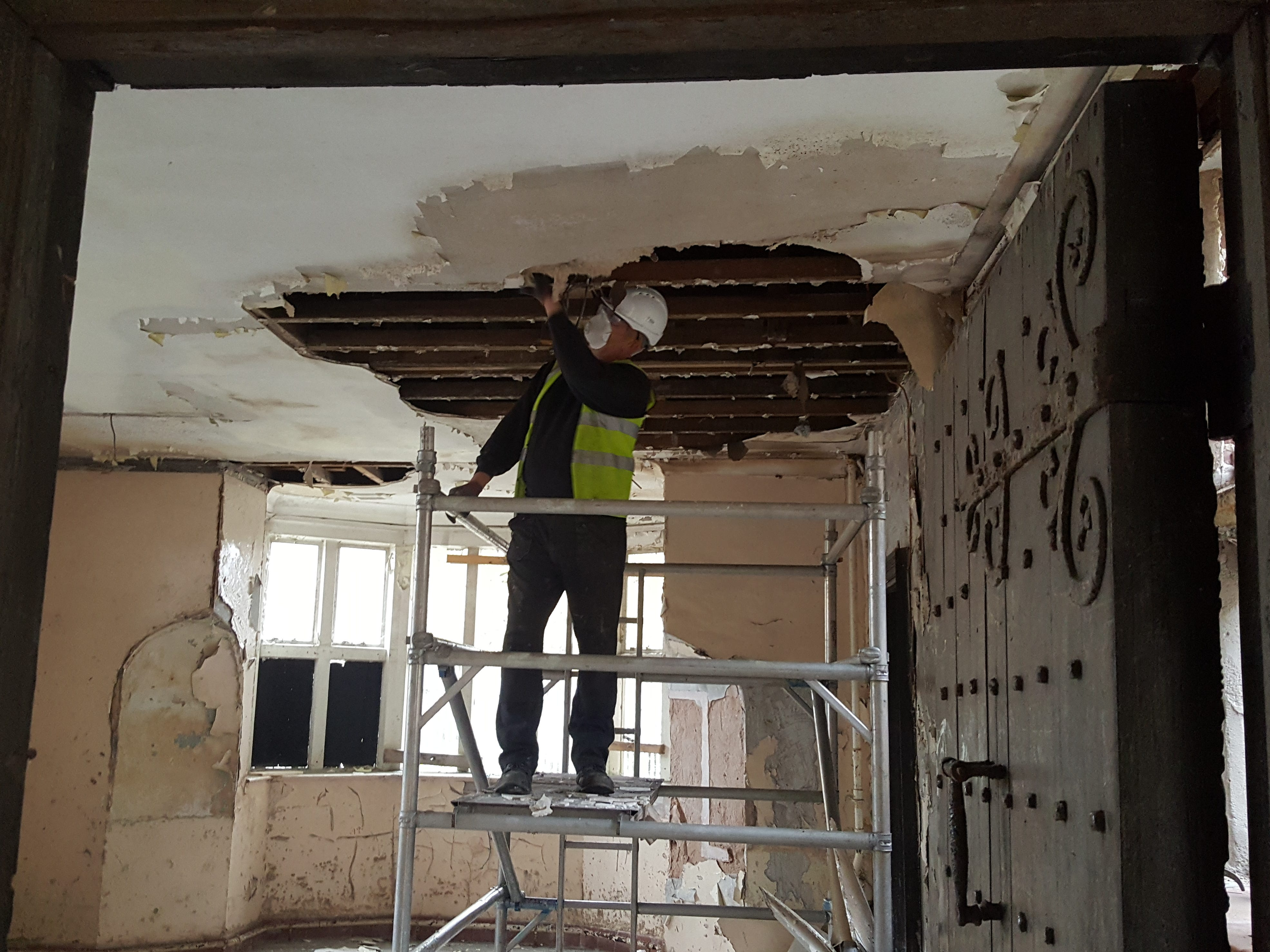 """A construction worker tears off the decaying ceiling of the """"chapel"""" in Hopwood Hall."""