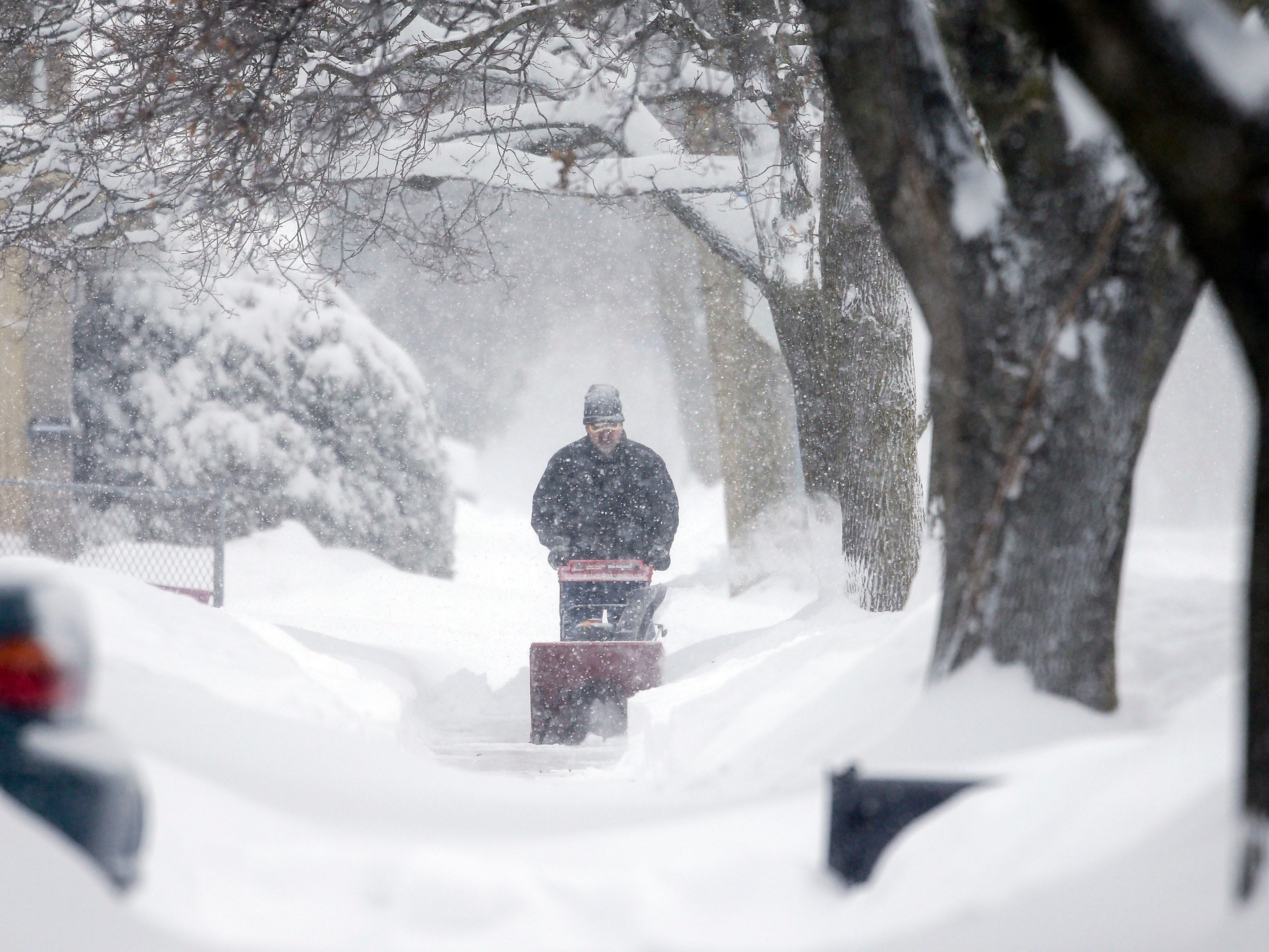 A Manitowoc resident snow blows the sidewalk as a snowstorm moves across the state in Manitowoc, Wis.