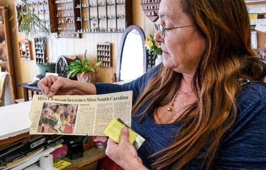 Donna Key of Village Alterations in Pendleton looks at a newspaper clipping of former Miss South Carolina Rachel Wyatt wearing a dress she made. Wyatt, who attended Wren High School and Clemson University, is now a Dallas Cowboy Cheerleader.