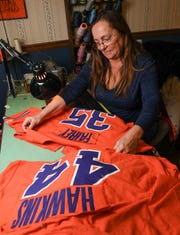 Donna Key at The Alteration Shop in Pendleton works on Clemson University baseball uniforms Wednesday. Key and coworkers get a variety of alteration items, including wedding, pageantry, and uniforms from Clemson.