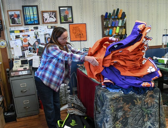 Donna Key at Village Alterations in Pendleton works on Clemson University baseball uniforms Wednesday. Key and coworkers get a variety of alteration items, including wedding, pageantry, and uniforms from Clemson.