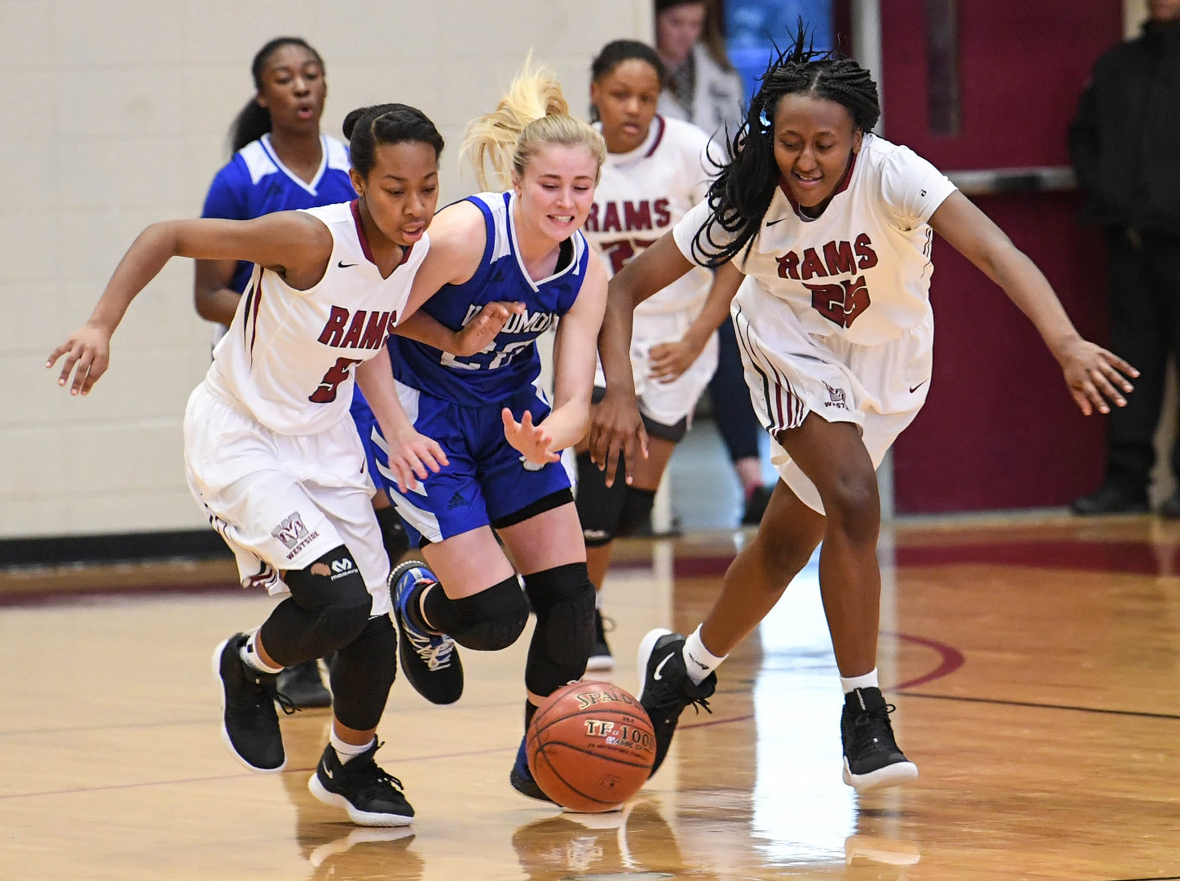 Westside senior Chelsea Adger(5), left, Woodmont senior Xan Rowland(20), and Westside junior Keyshuna Fair(25) reach for a loose ball during the first quarter at Westside High School in Anderson on Tuesday.