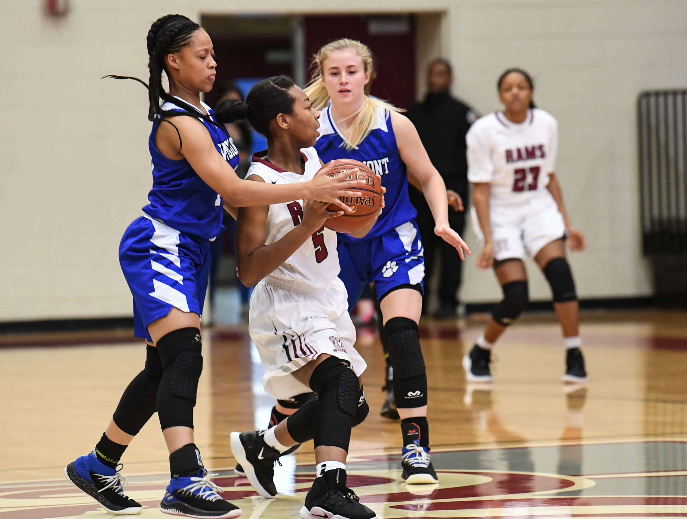 Westside senior Chelsea Adger(5), middle, picks up a loose ball near Woodmont senior Xan Rowland(20), right, and Woodmont senior Kitara Henry(33) during the first quarter at Westside High School in Anderson on Tuesday.