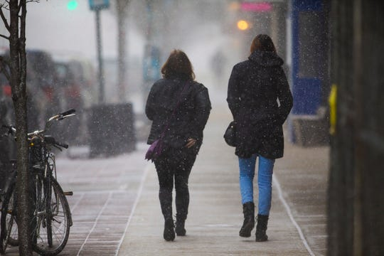 Shoppers make their way through the snow burst as they walk on Cookman Ave in Asbury Park.