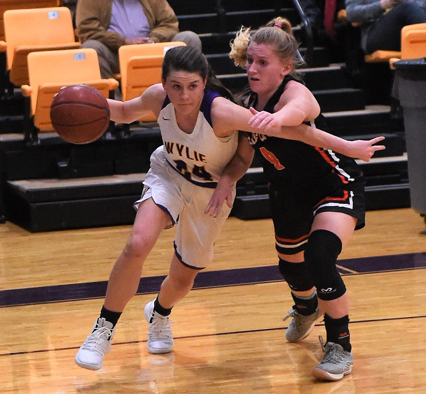 Wylie guard Mary Lovelace (24) drives past Aledo's Riley Sale (4) during Tuesday's District 4-5A contest at Bulldog Gym. Lovelace scored 15 points in the 51-47 overtime loss.