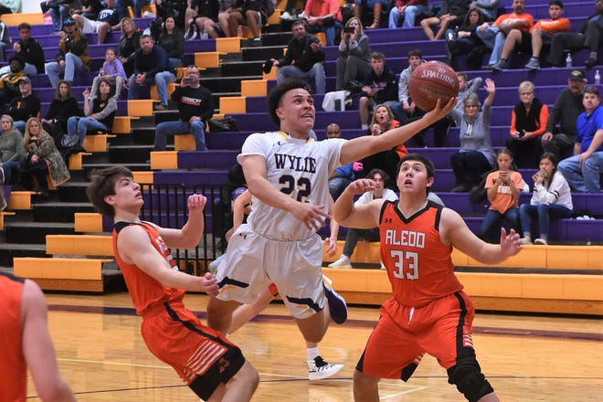 Wylie guard Shayden Payne (22) goes into the air for a layup against Aledo in District 4-5A play at Bulldog Gym on Tuesday, Jan. 29,  2019. The Bulldogs won 60-43 to pull into a tie for second.