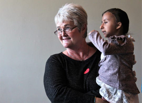 Marilyn Todd, of New Life Children's Home in Villa Nueva, Guatemala, holds 11-year-old Michelle at a reception Sunday afternoon in Slaton. Michelle recently received medial care in Houston.