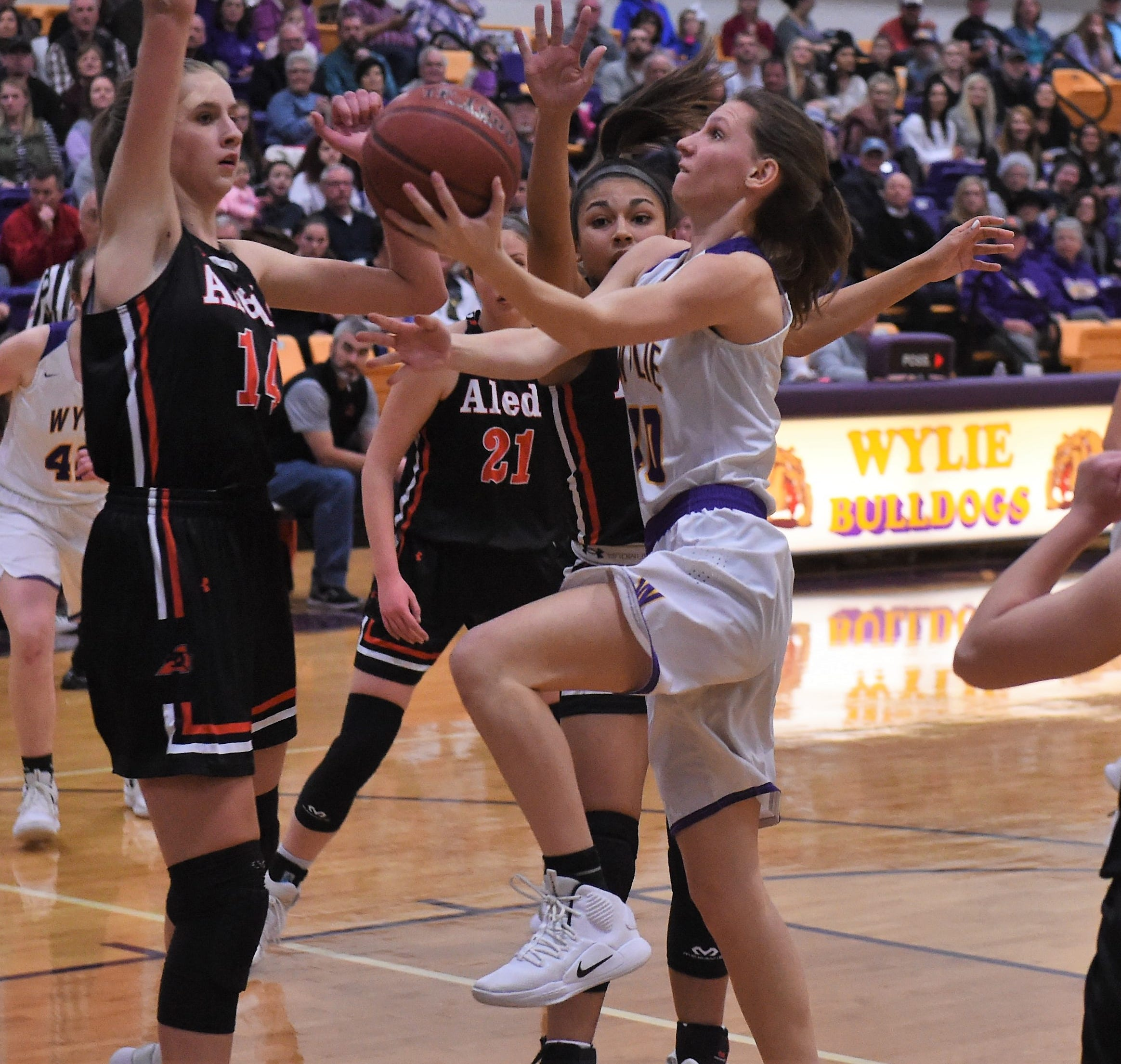 Wylie's Abbey Henson (10) goes up for a shot around a pair of Aledo defenders during Tuesday's District 4-5A contest at Bulldog Gym. Henson scored 15 points in the 51-47 overtime loss.