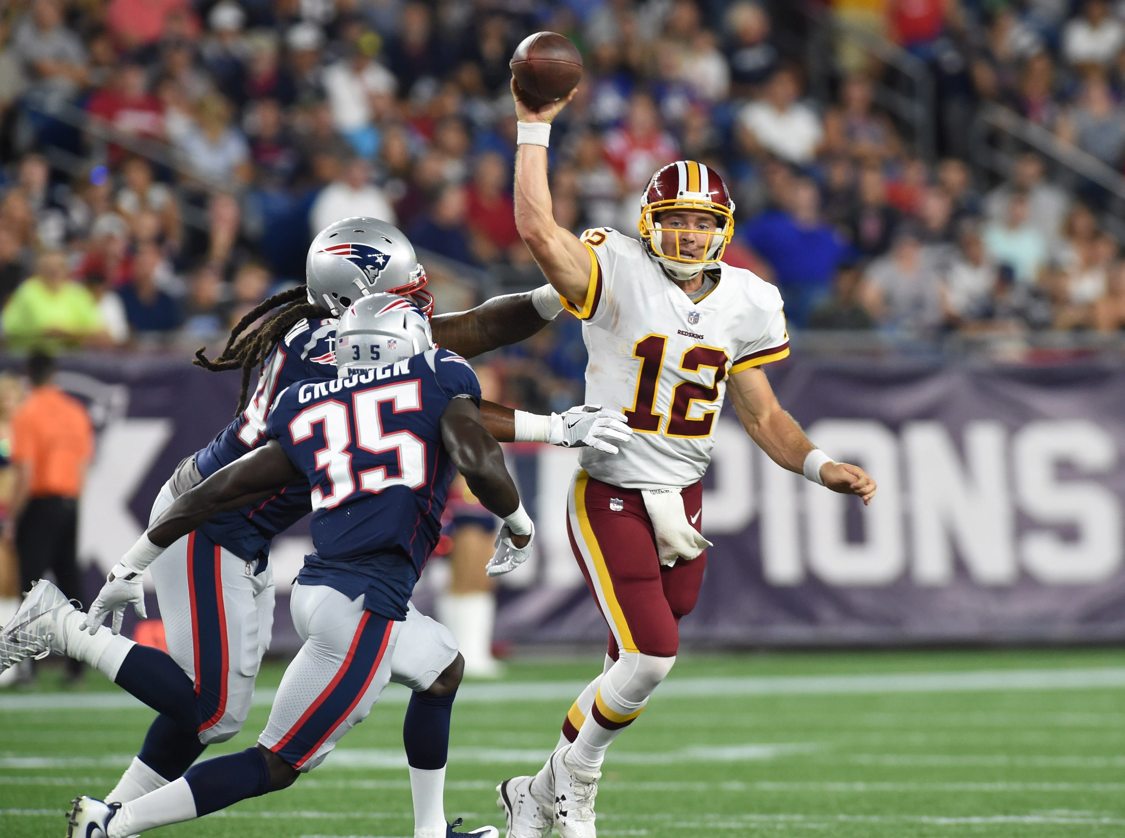 Aug 9, 2018; Foxborough, MA, USA; Washington Redskins quarterback Colt McCoy (12) throws the ball away while being pursued by New England Patriots defensive back Keion Crossen (35) during the first half at Gillette Stadium. Mandatory Credit: Bob DeChiara-USA TODAY Sports