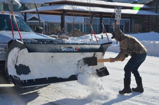 Nick Blaskie of Battle Creek Glassware clears hardened snow off his plow in downtown Battle Creek on Wednesday.