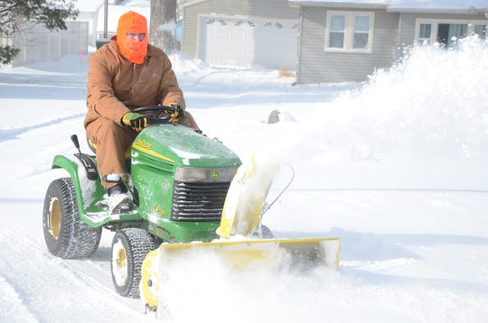 Kyle Klein was clearing snow Wednesday from his neighbors' driveways despite the cold.