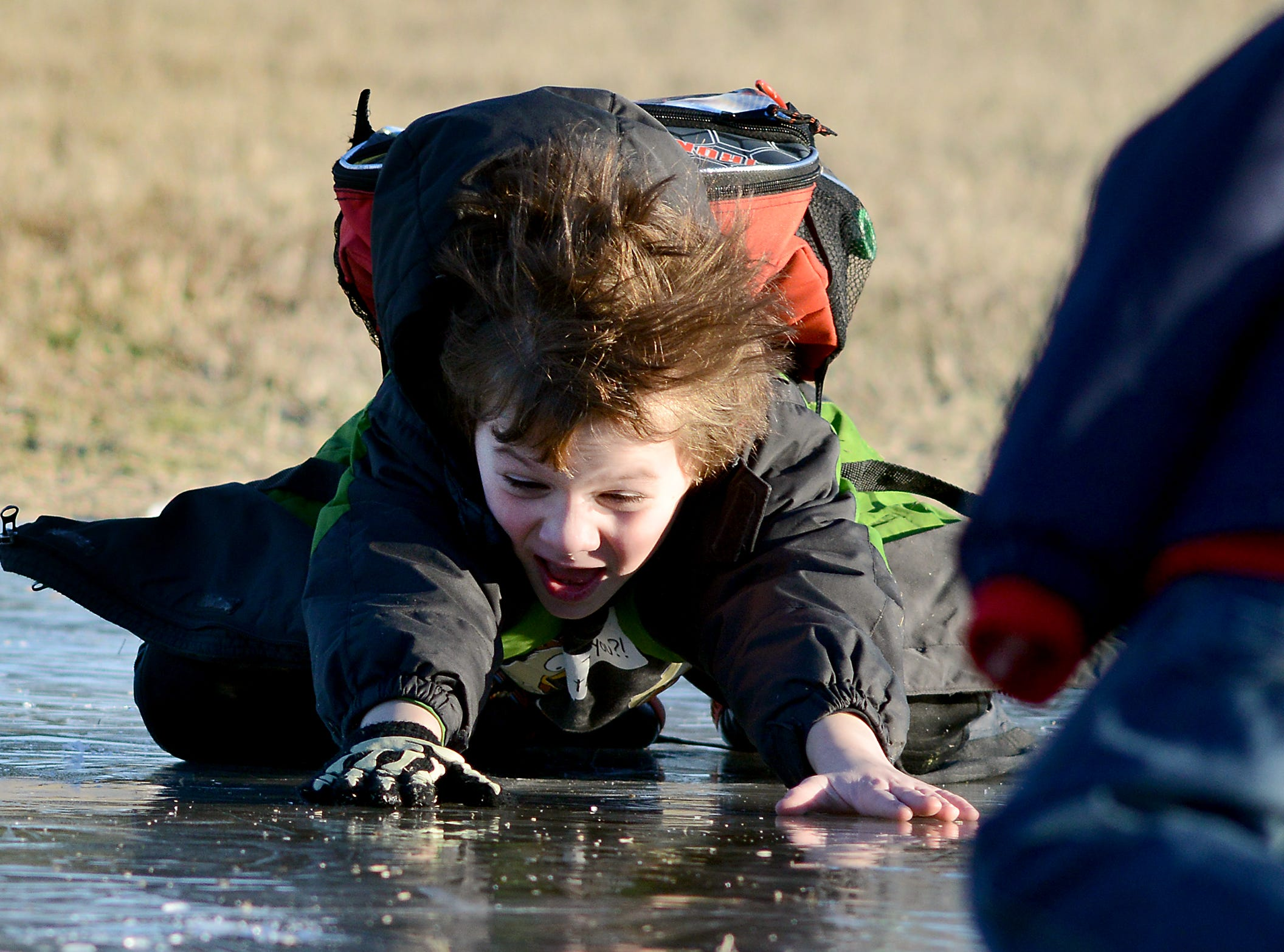 Tobias Walas, 7, and other Ocean City Elementary School students turned a frozen puddle into an ice slide after school Tuesday afternoon at the school in West Ocean City. 2013.
