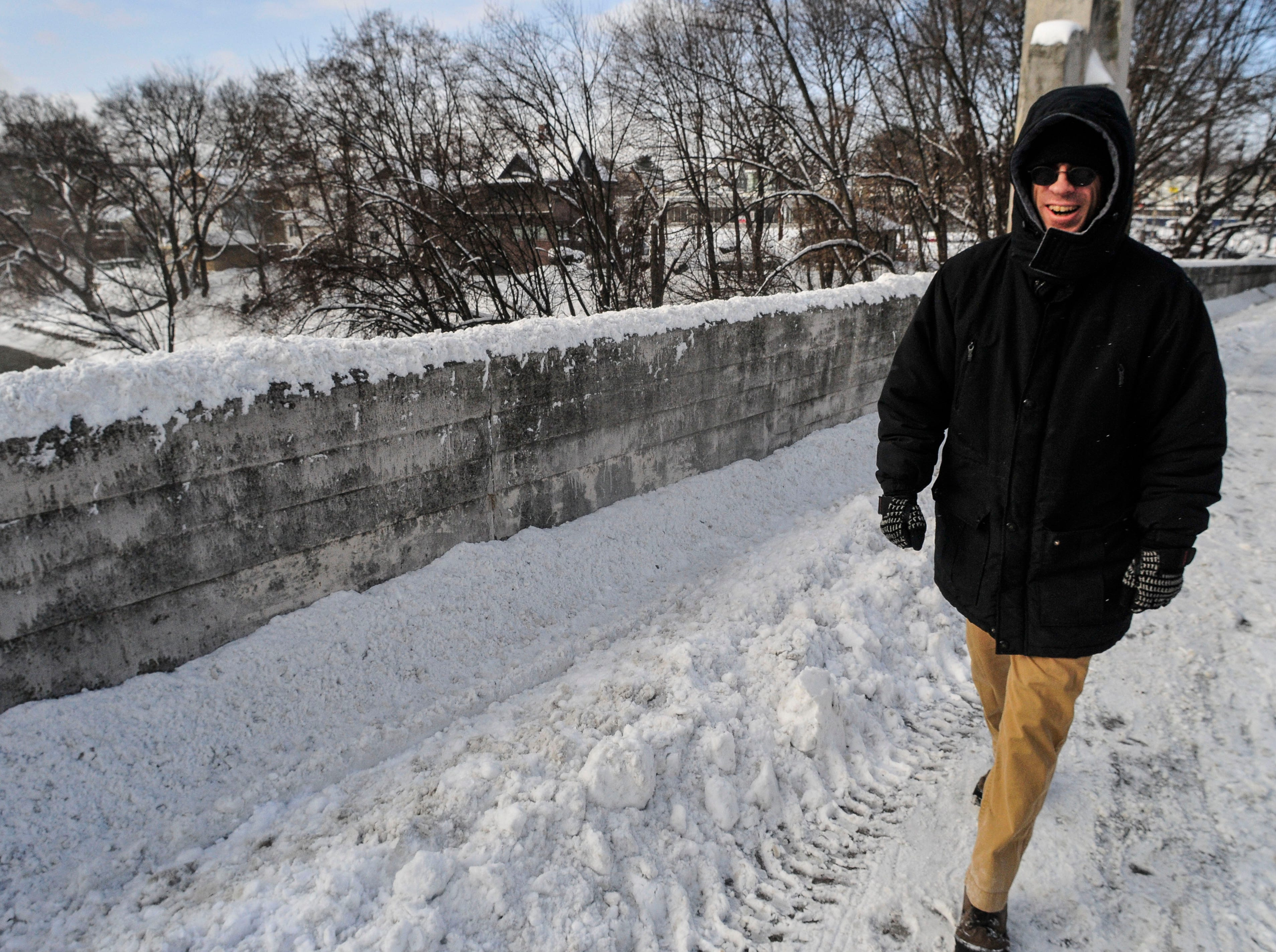 Mark Loeffler, from Binghamton, walks across the Clinton Street Bridge on Friday morning on his way to the bank as temperatures dip below zero. 2014.