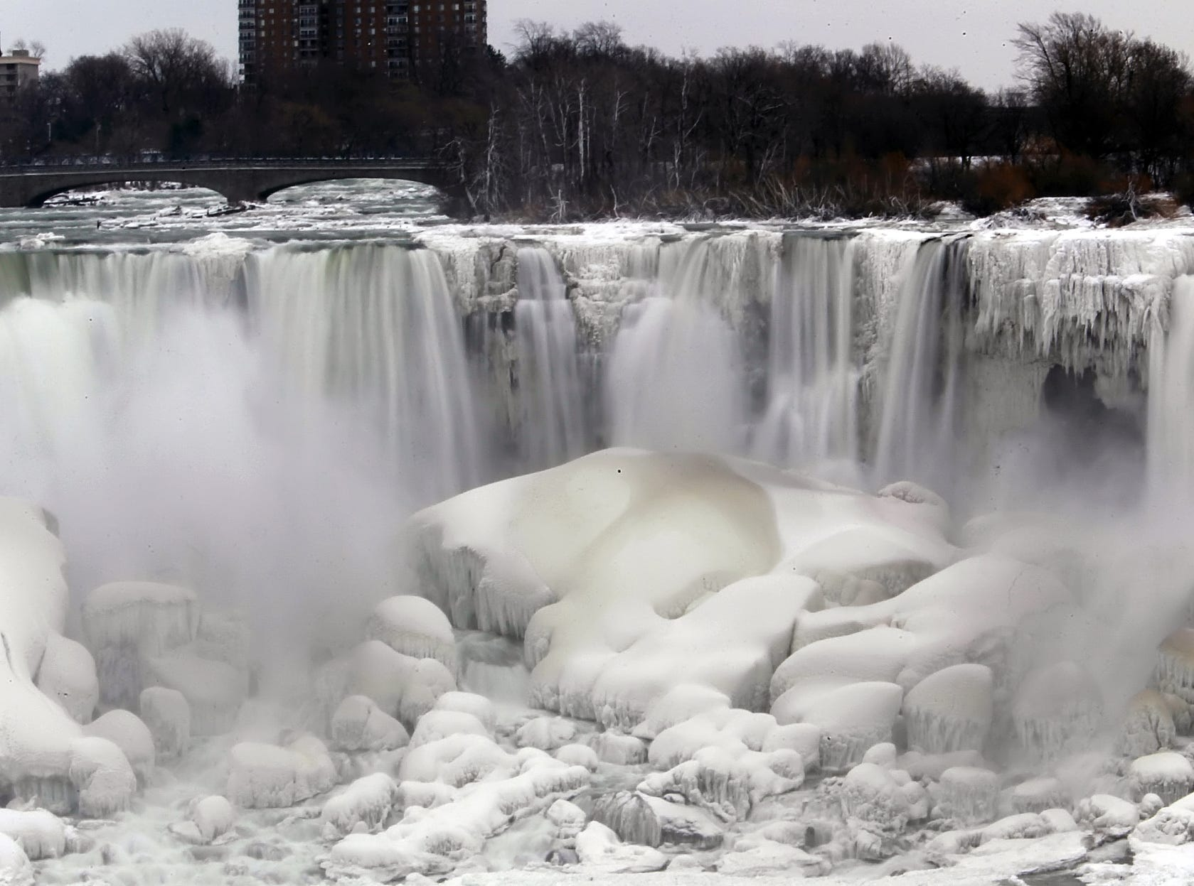 "The U.S. side of Niagara Falls has begun to thaw after being partially frozen from the recent ""polar vortex"" that affected millions in the U.S. and Canada, Friday, Jan. 10, 2014 in Niagara Falls, N.Y., as seen from the Canadian side of the falls."
