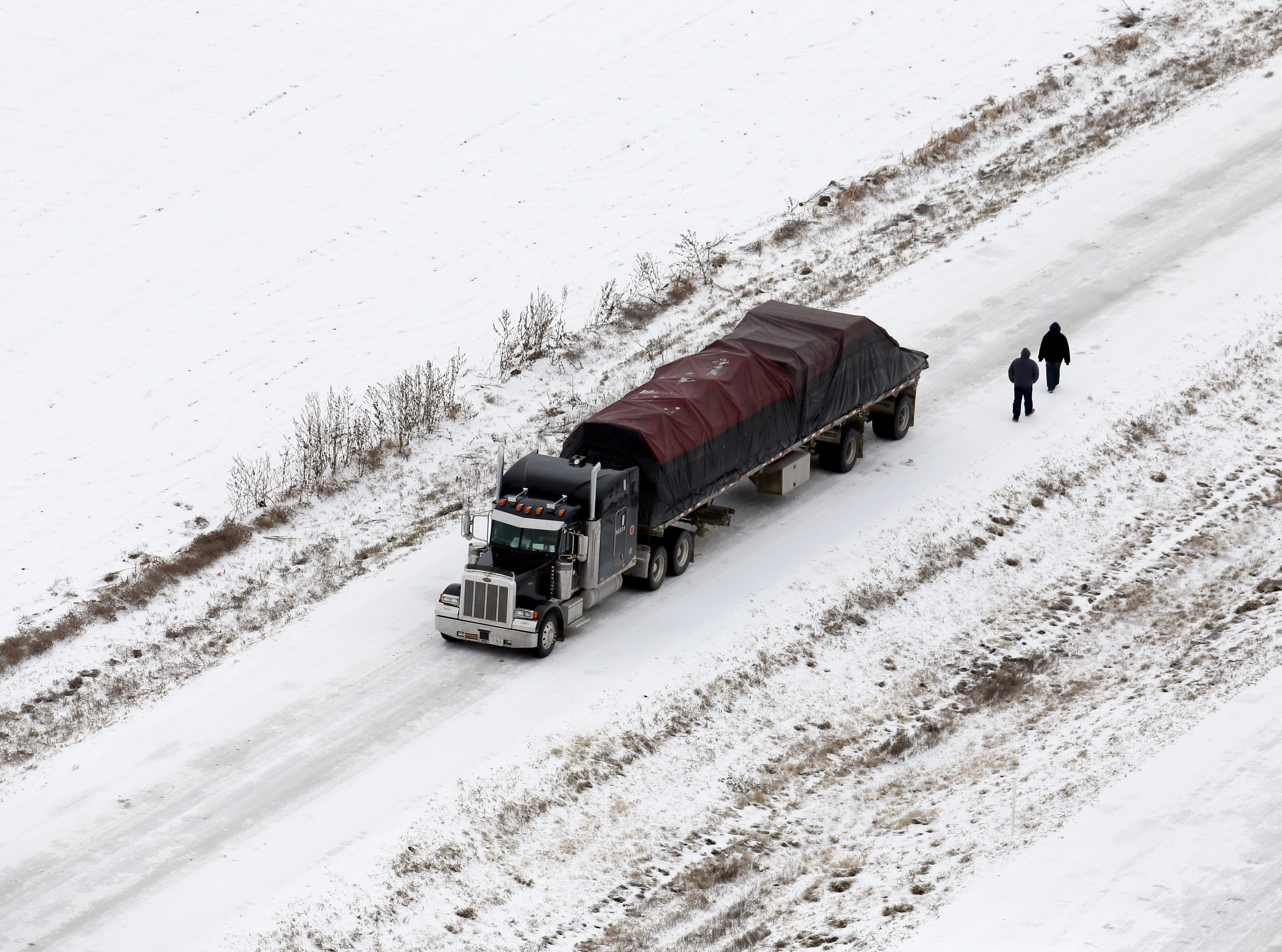 Persons walk by a tractor trailer truck headed south on an ice covered service road along IH-35E, Saturday, Dec. 7, 2013, near Sanger, Texas.