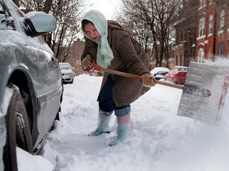 Gilda Mosely digs her car out from the snow outside her home on Tuesday, Jan. 7, 2014, in Soulard, Mo. Tuesday was the worst cold snap in nearly two decades for Missouri.