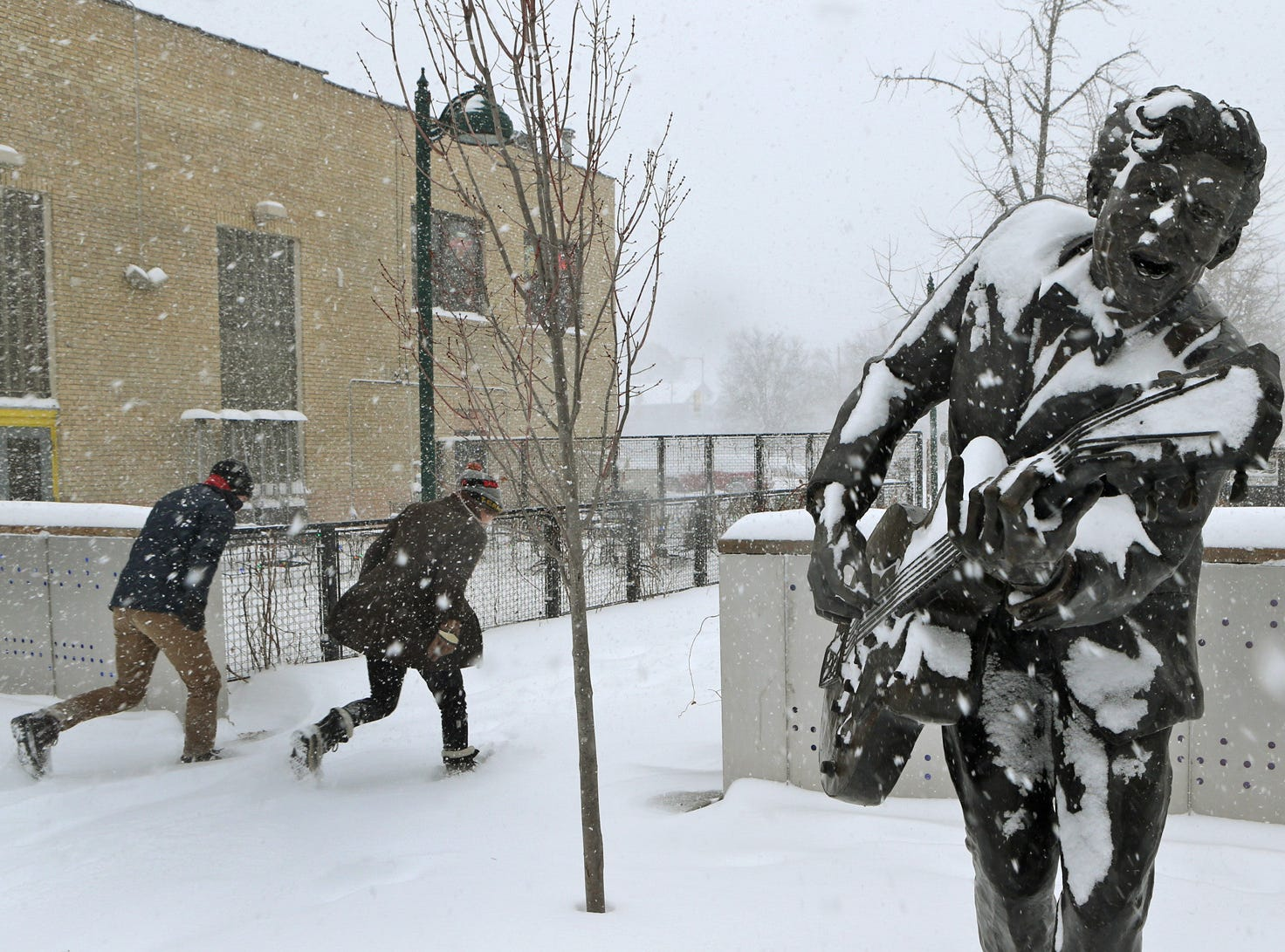 Two people duck into the blowing snow as they leave the U City Loop next to the statue of Chuck Berry on Sunday morning, Jan. 5, 2014, in St.ÊLouis.  Heavy snow combined with strong winds and bitter cold created a dangerous winter mix Sunday over much of Missouri.