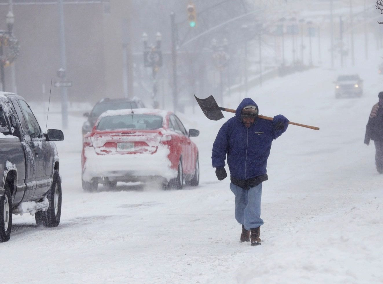 "Peter Vasquez of Flint carries his shovel while walking through the drifting snow along a plowed Saginaw Street in downtown Flint, Mich., on Monday Jan. 6, 2014 after a snowstorm dumped several inches if snow in the area.   A whirlpool of frigid, dense air known as a ""polar vortex"" descended Monday into much of the U.S."