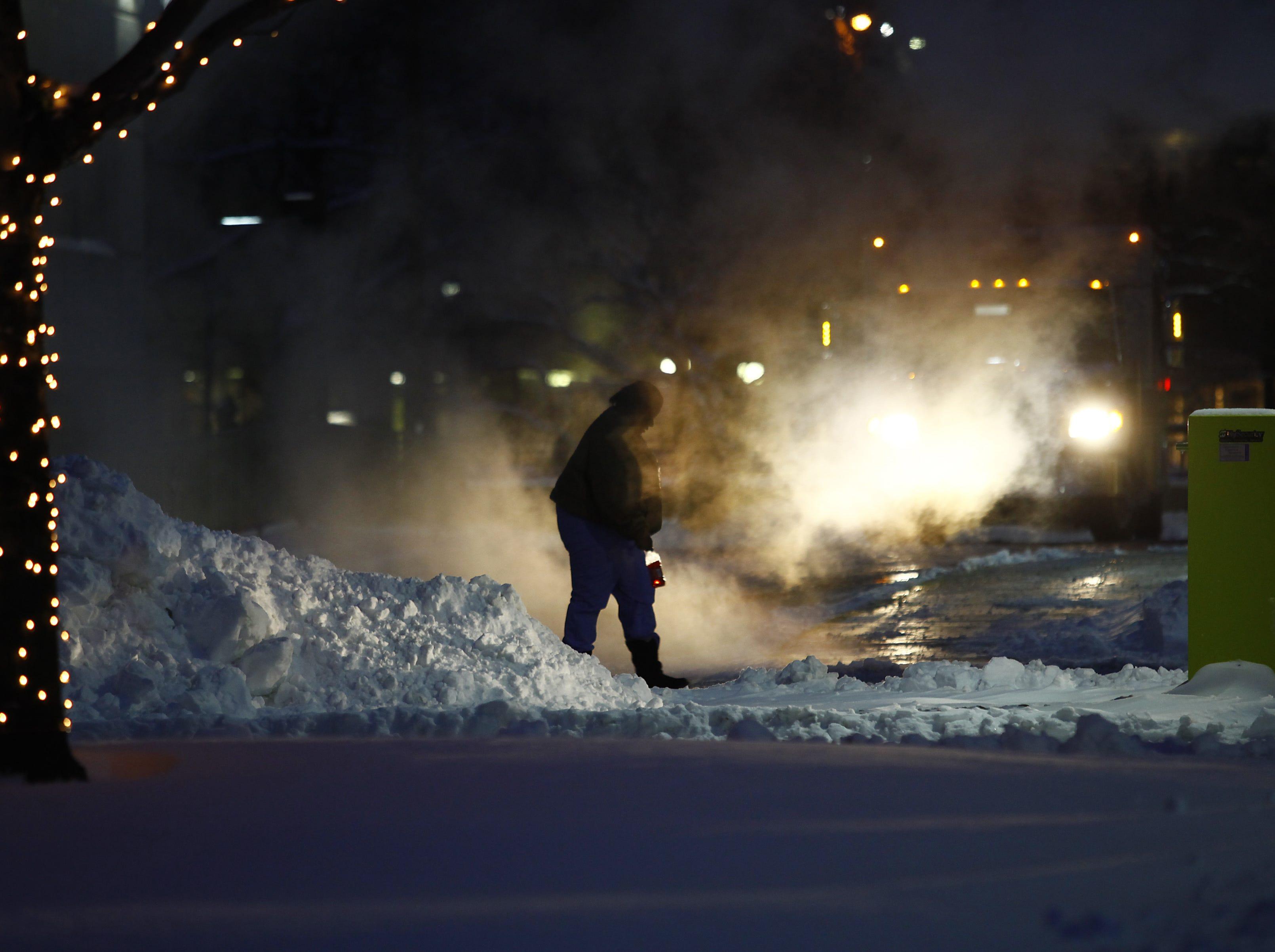 "A woman navigates around several inches of snow and steam as the area deals with record breaking freezing weather January 6, 2014 in Detroit, Michigan. Michigan and most of the Midwest received their first major snow storm of 2014 last week and subzero temperatures are expected most of this week with wind-chill driving temperatures down to 50-70 degrees below zero. A ""polar vortex"" weather pattern is bringing some of the coldest weather the U.S. has had in almost 20 years."