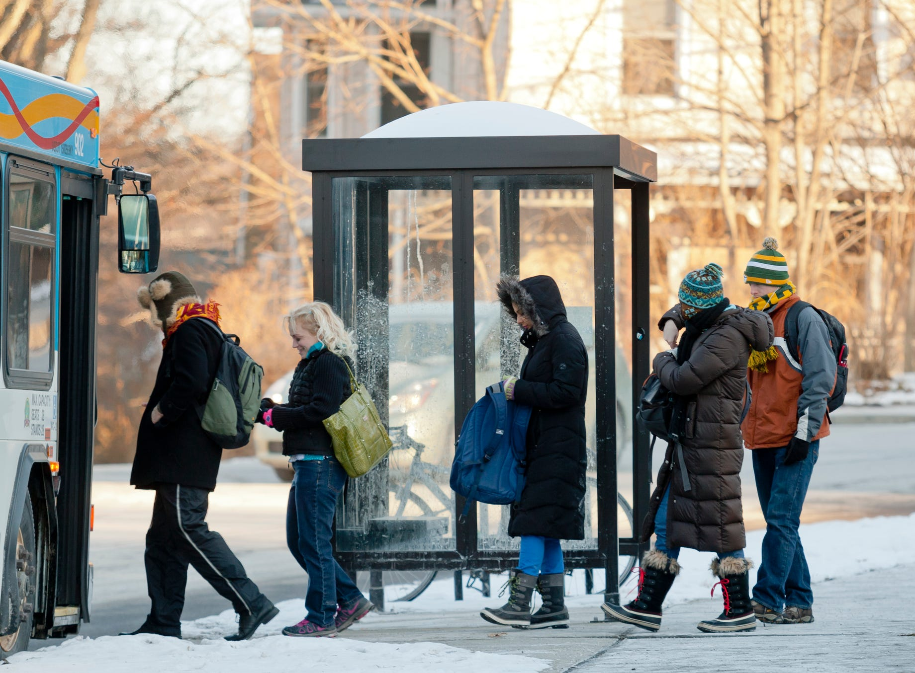 Tompkins Consolidated Area Transit passengers board the number 10 bus after waiting in the zero degree cold Tuesday morning at the intersection of Linn and University Streets in Ithaca. 2014.