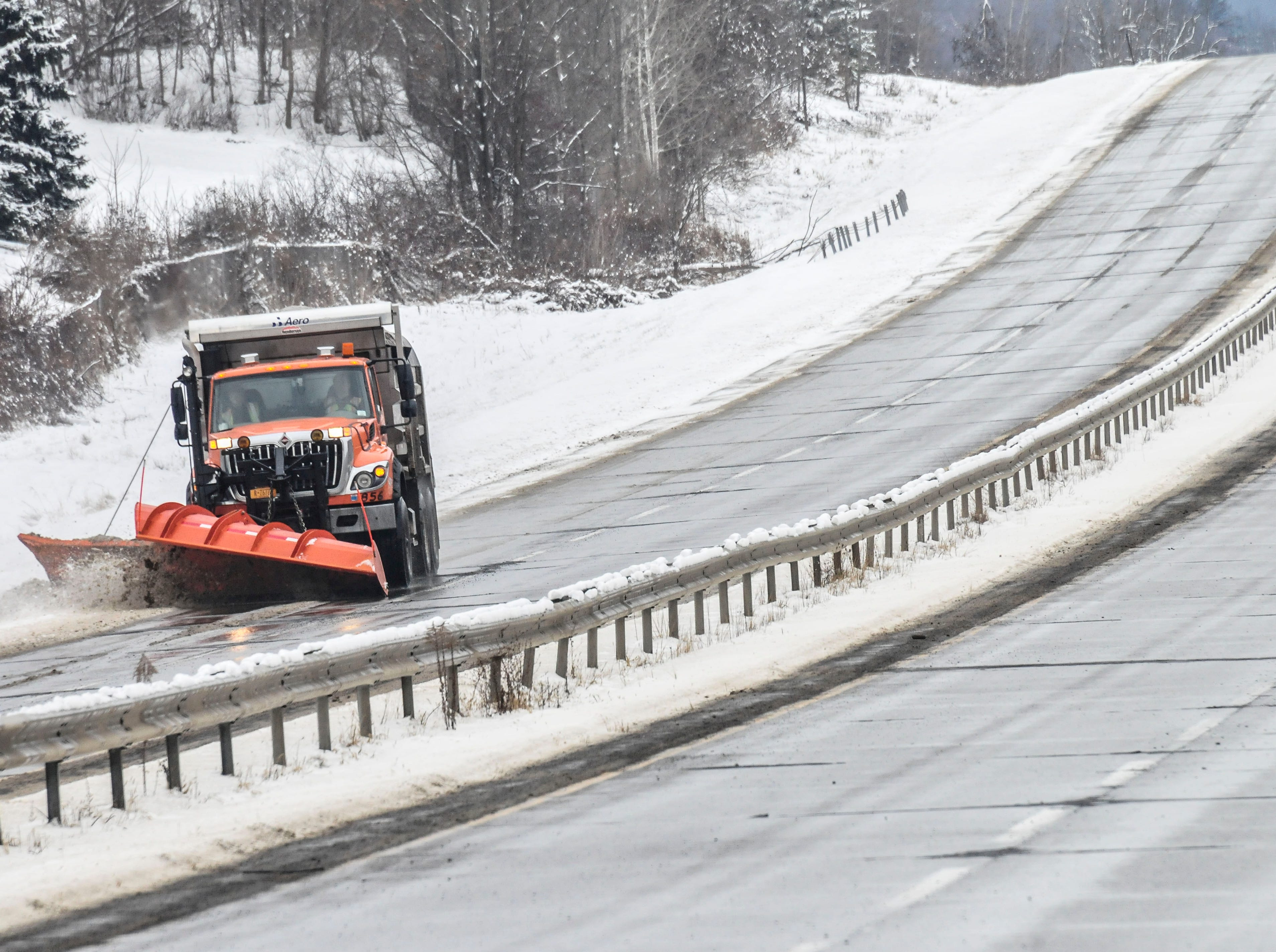 A snow plow removes snow from the shoulder of Airport Road on Thursday.