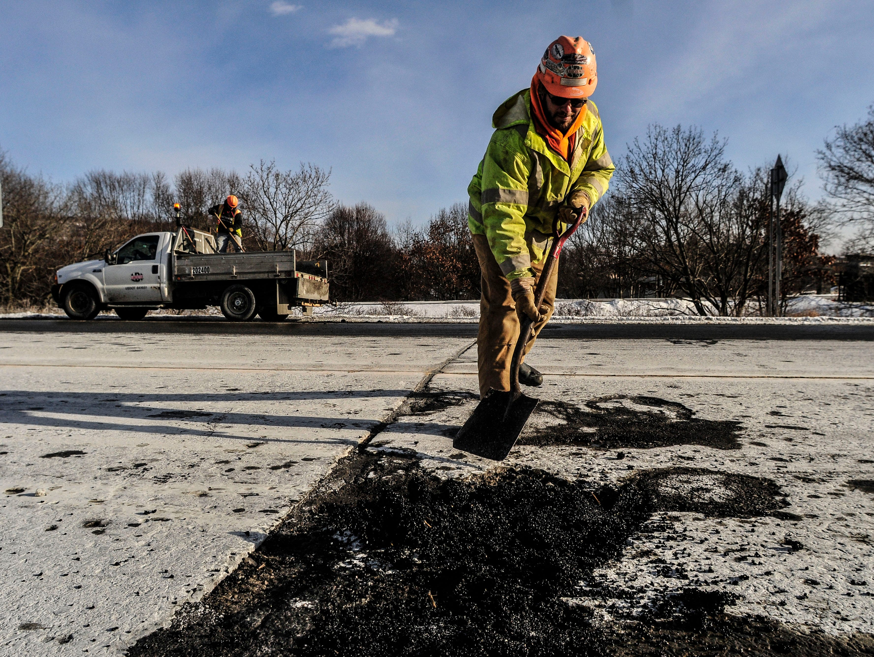 John Hoover, from Windsor, employee at Lancaster Development Inc., puts asphalt into potholes on Front Street in Binghamton during a frigid cold Tuesday in 2014.
