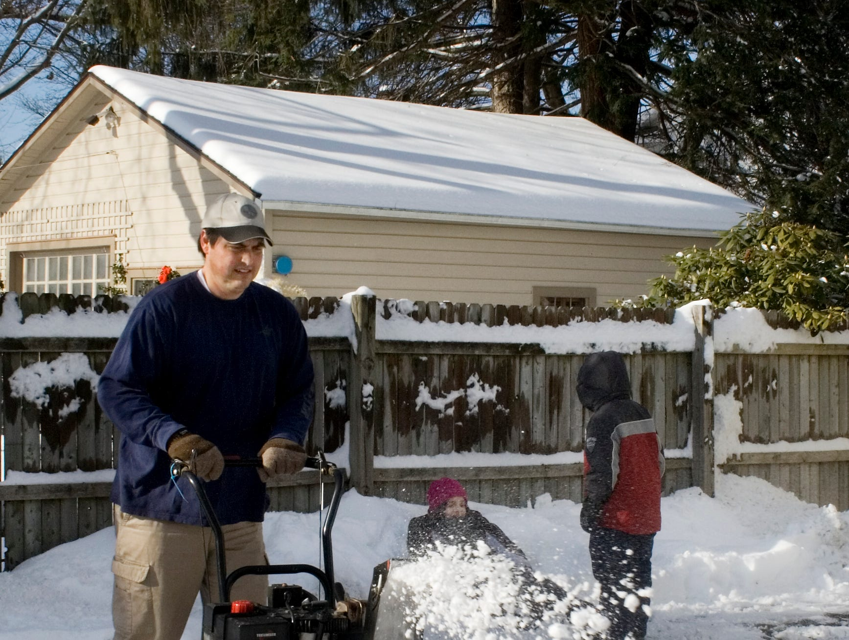Roger Curtis of West Gray Street in West Elmira uses a snowblower to clear his driveway Sunday afternoon while his children Megan and Ethan play in the snowbank.