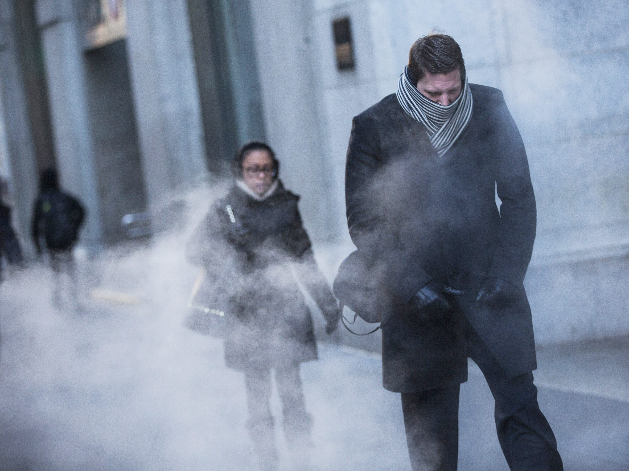 A man clenches his fists while walking past a steam vent in New York. A polar vortex has descended on much of North America, coming down from the Arctic, bringing record-freezing temperatures across much of the country.