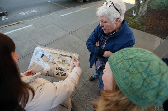 Christina Doherty, Emily Gustafson and Christine Perkins look at a newspaper article that featured the planting of the tree in 1967.