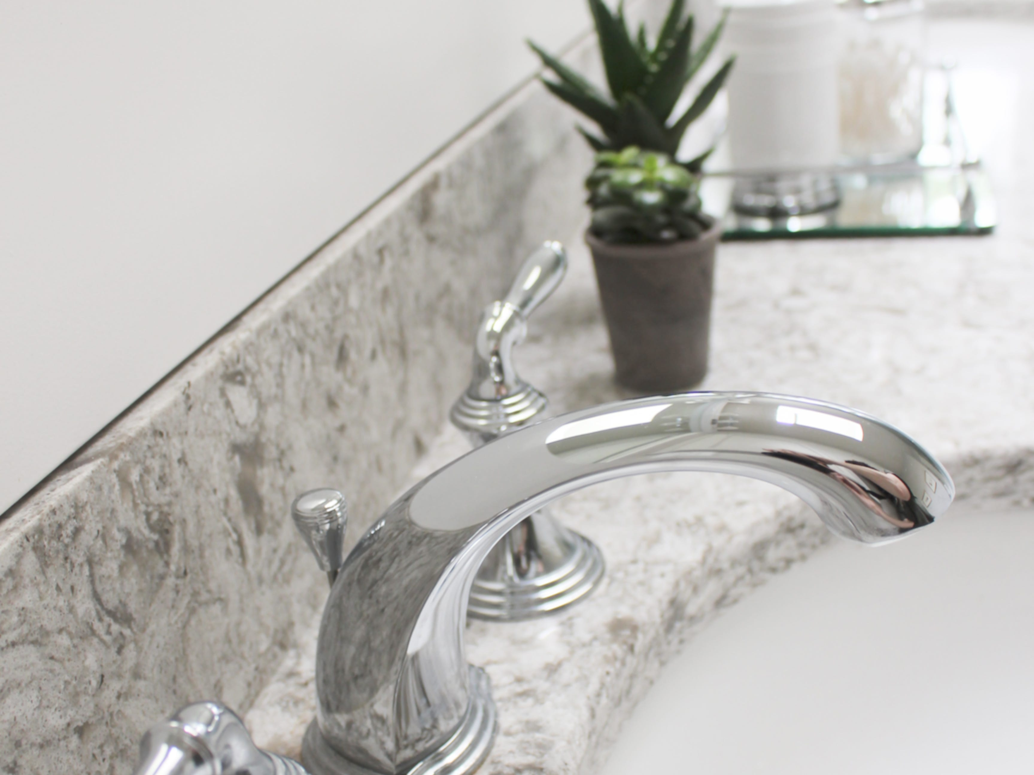 The shimmer from the glass in the mosaic tile is repeated in the polished chrome faucet.