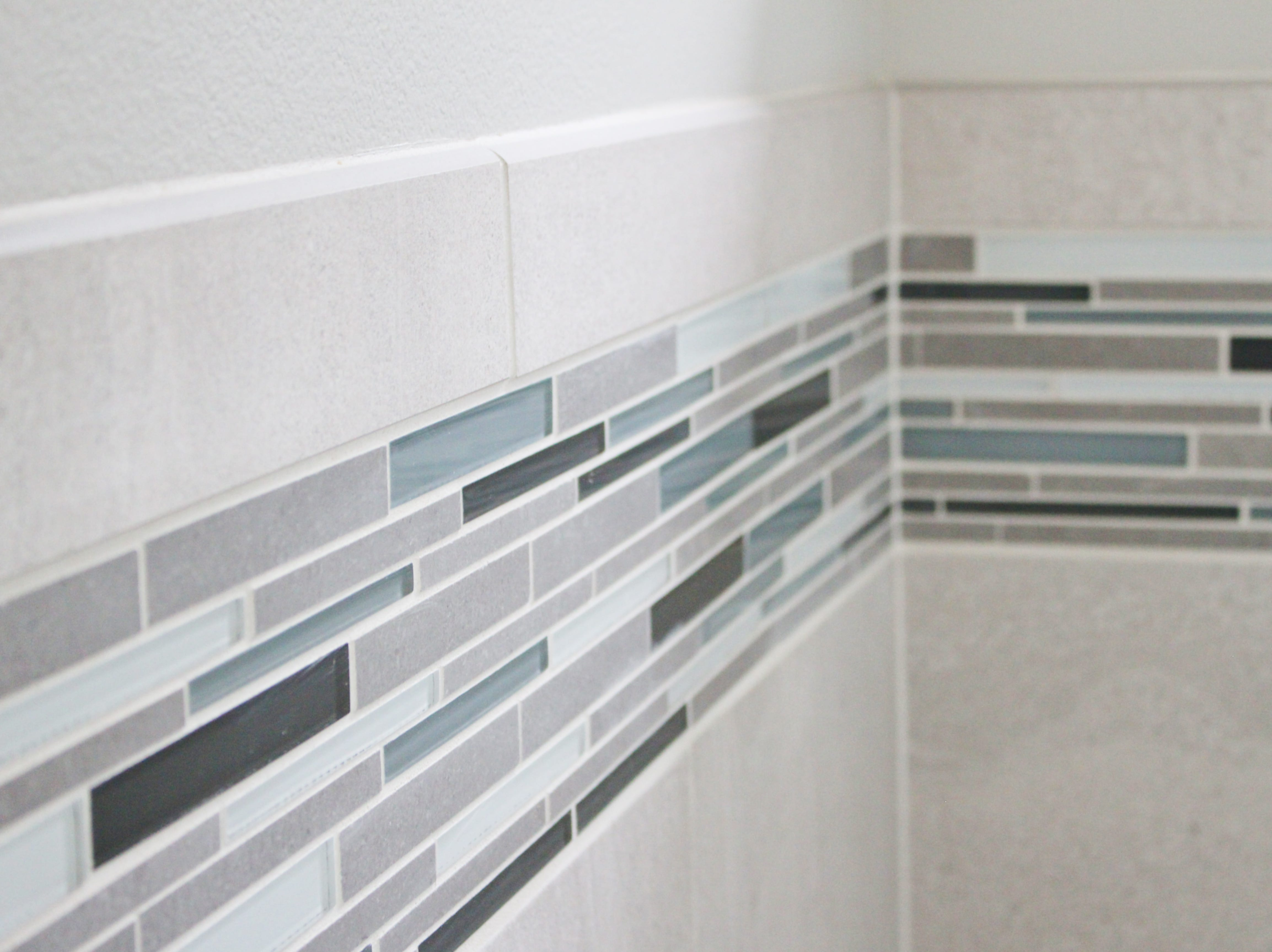 The glass of the mosaic tile is a combination of cool gray, earthy beige, and subtle blue-gray.