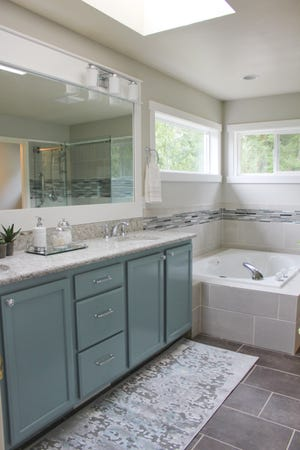 The blue-gray color from the mosaic tile is repeated in the painted vanity cabinet and in the rug.