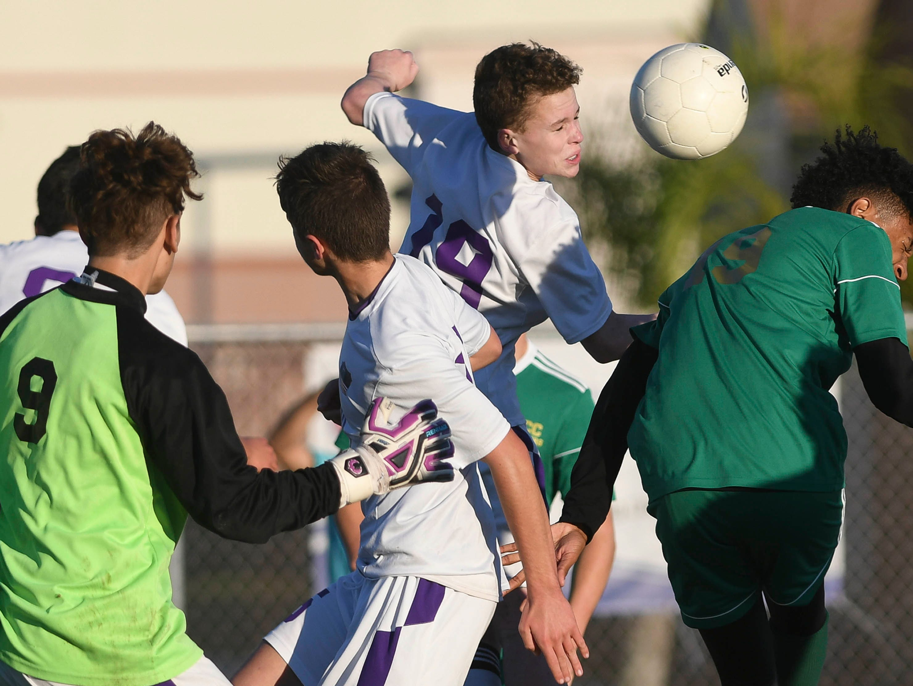 Space Coast and MCC players vie for a header during Tuesday's District 8, Class 2A semifinal at Cocoa Beach High.