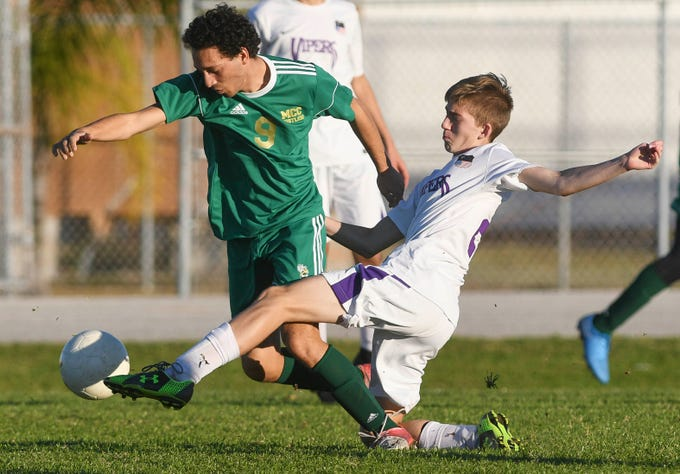 Ethan Chicklinski of Space Coast tackles the ball away from Gabe Velez-Wyche of Melbourne Central Catholic during Tuesday's District 8, Class 2A semifinal at Cocoa Beach High.