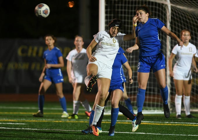 Titusville's Raelyn Prince heads the ball away from Lexy Denaburg of Merritt Island during Tuesday's District 12, Class 3A semifinal.