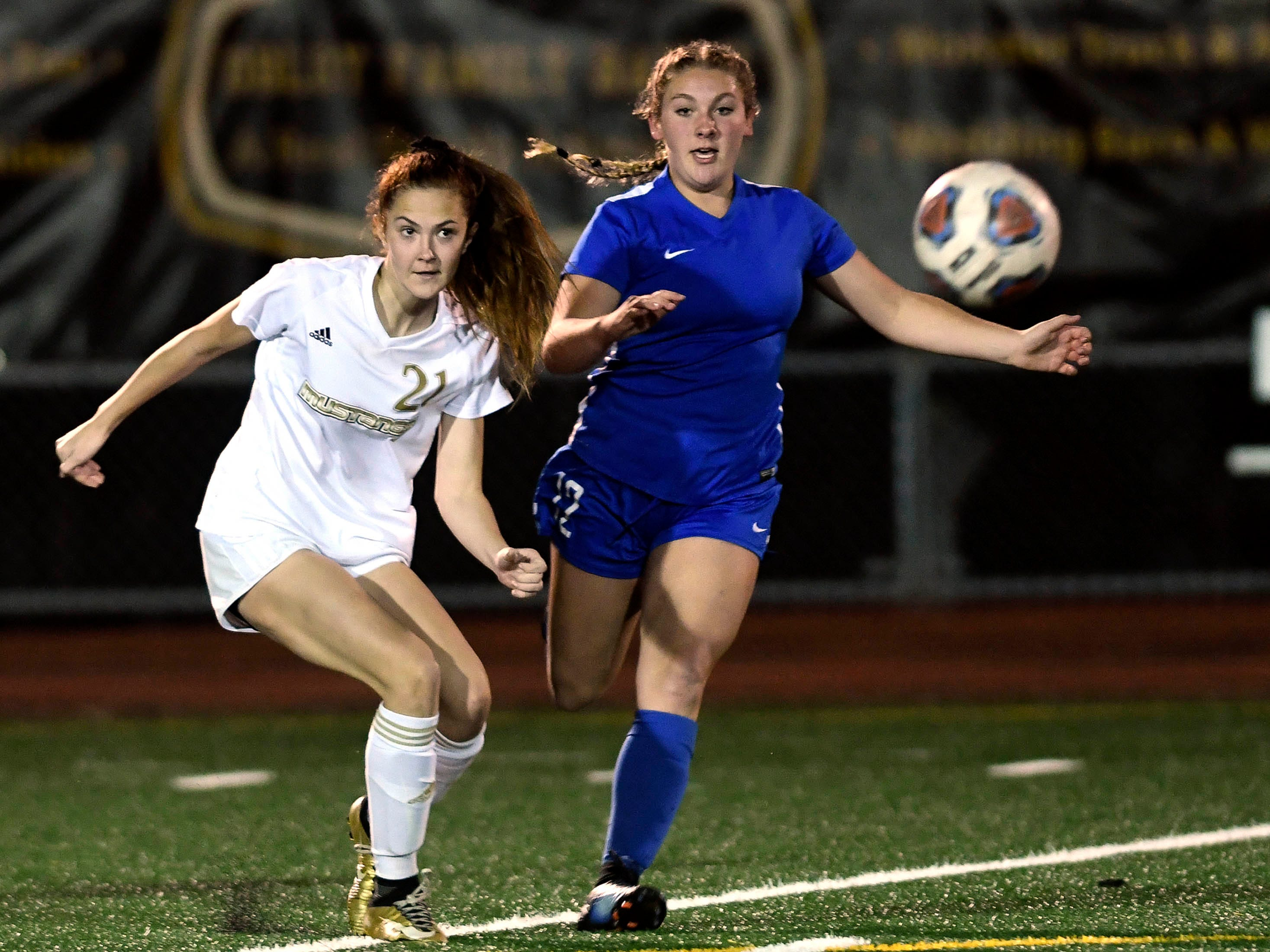 Ashleigh Sweat of Merritt Island drives the ball away from Macey Neal of Titusville during Tuesday's District 12, Class 3A semifinal game.