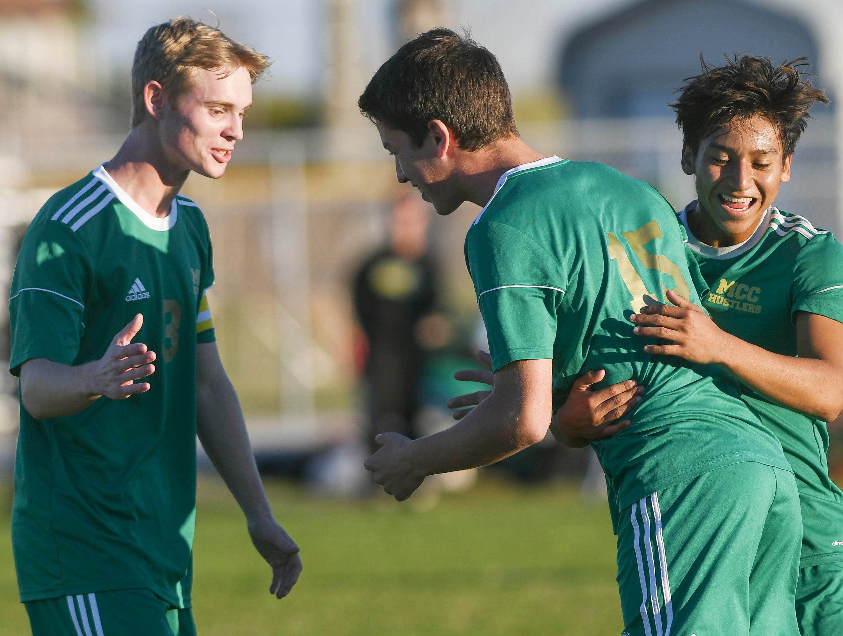 Ed Nekrasov of Melbourne Central Catholic is congratulated by teammates Tyler Keller (left) and Junior Acuna (right) after scoring a goal in Tuesday's District 8, Class 2A semifinal against Space Coast at Cocoa Beach High.