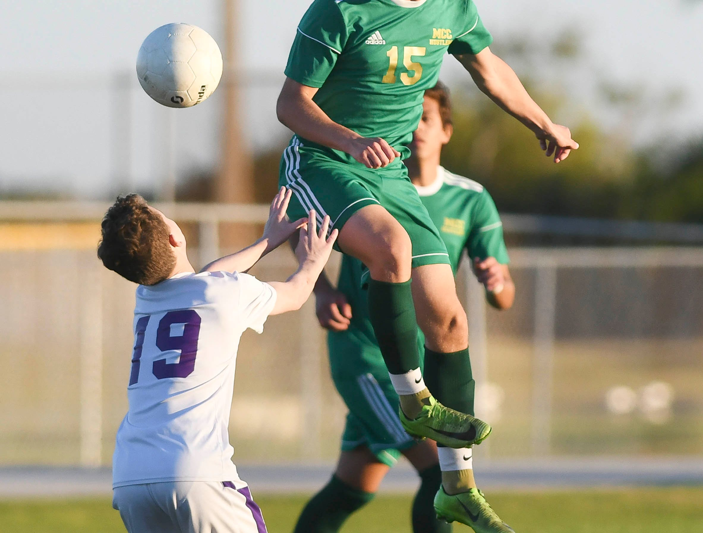 Ed Nekrasov of Melbourne Central Catholic directs the ball away from Colby Karpowich of Space Coast during Tuesday's District 8, Class 2A semifinal at Cocoa Beach High.