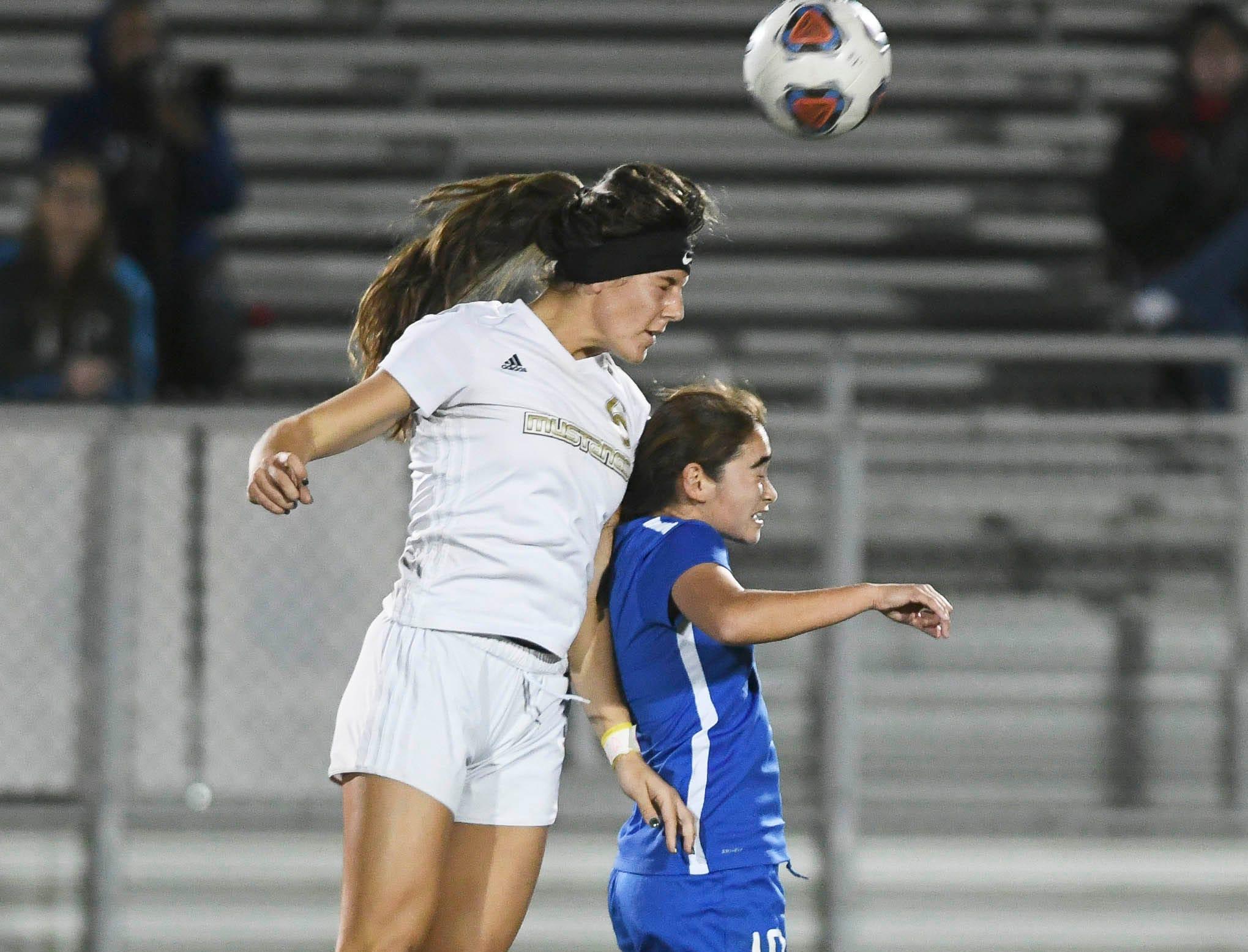 Lexy Denaburg of Merritt Island heads the ball over Adrianne Gutman of Titusville during Tuesday's District 12, Class 3A soccer semifinal.