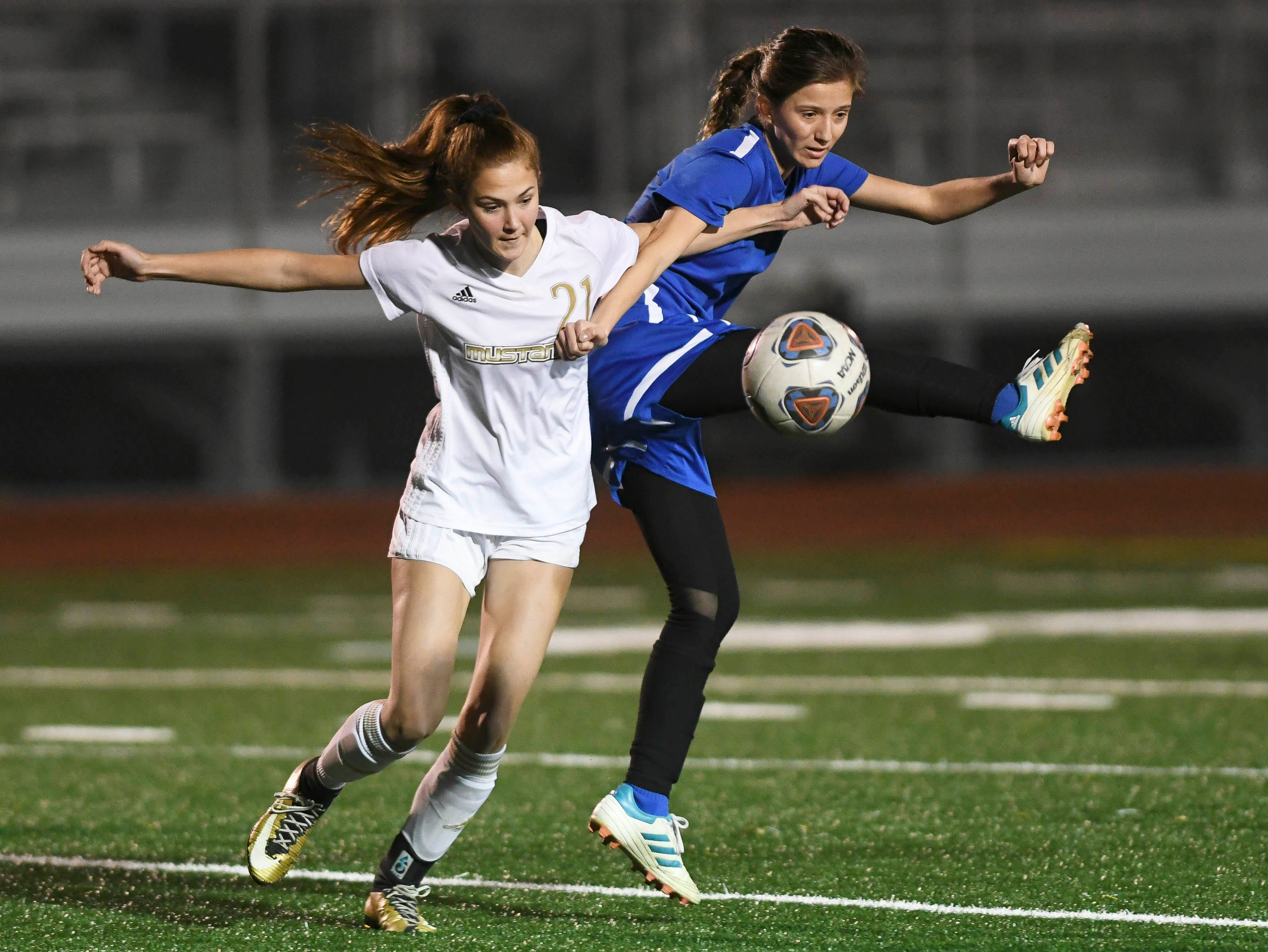 Ashleigh Sweat of Merritt Island and Adrianne Gutman of Titusville fight for the ball during Tuesday's district soccer semifinal.