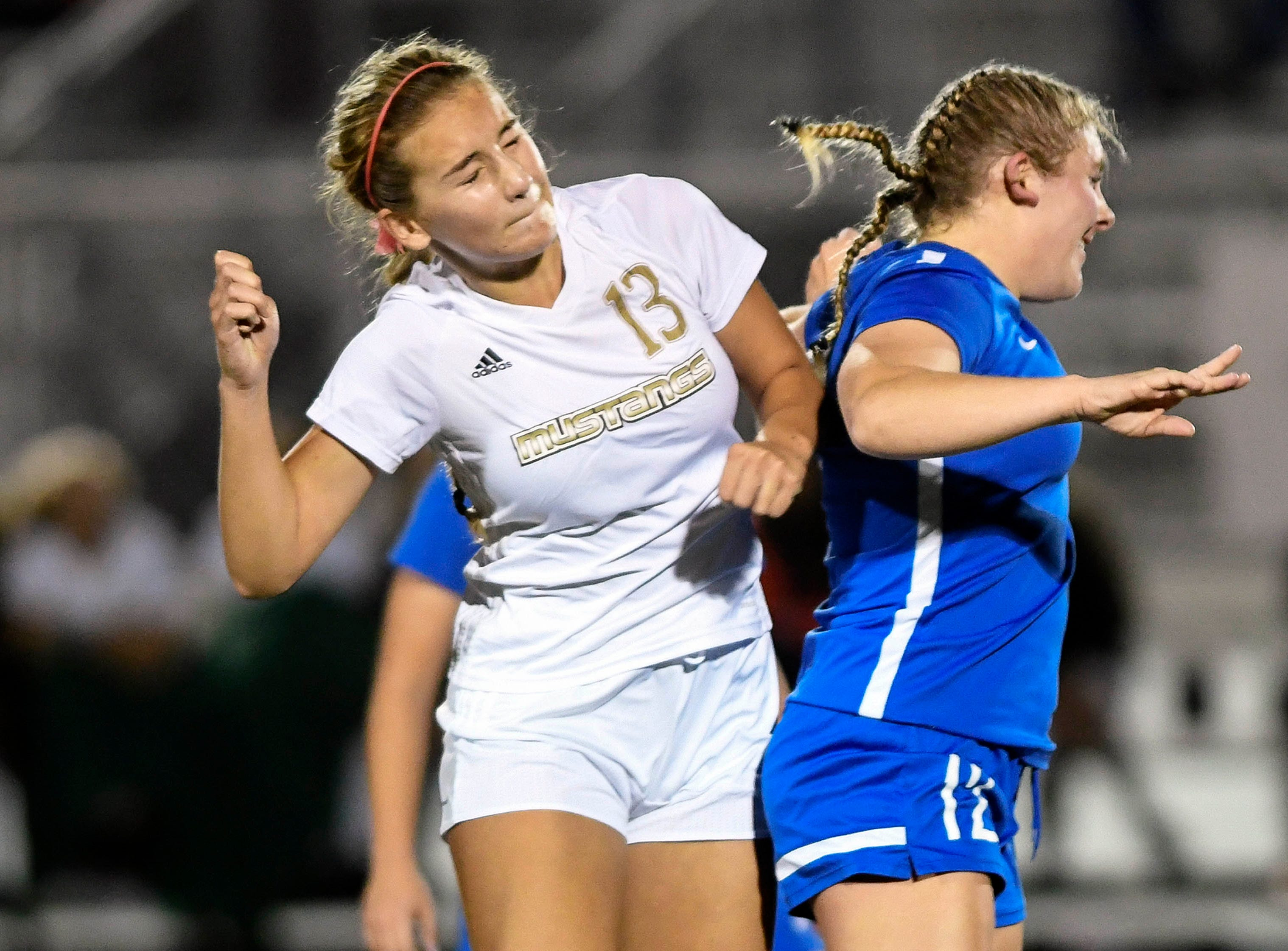 Karys Verpaele of Merritt Island and Macey Neal of Titusville go for a header during Tuesday's District 12, Class 3A soccer semifinal.