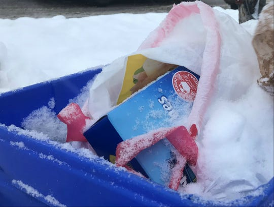 A plastic trash bag contains items left out for recycling on Maple Street in Burlington on Wednesday, Jan. 30, 2019.