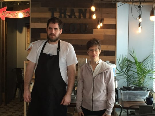Employees Ian MacLeod and Kate Bove stand inside the Perky Planet Coffee Shop in Burlington on Jan. 30, 2019.