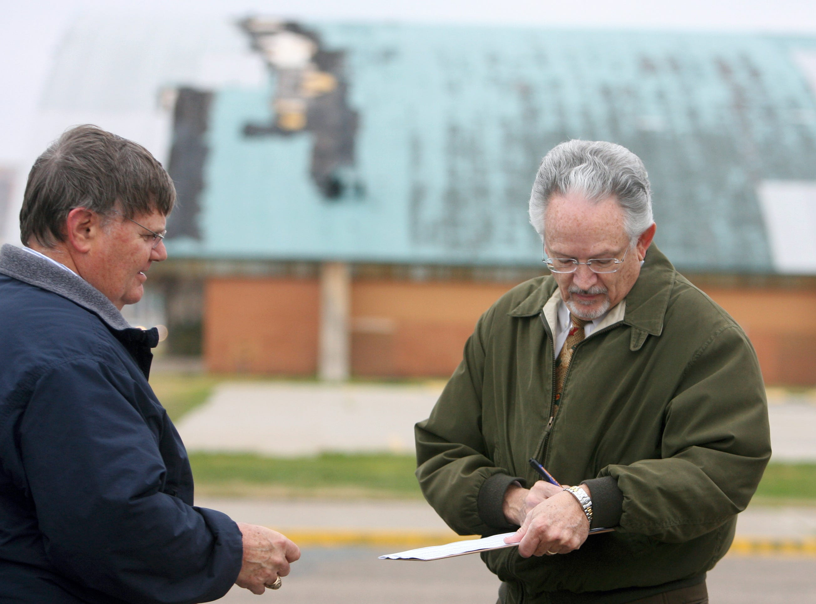 "Joe McComb (left) stands by as Cy Richards signs a petition in February 2009 in the parking lot of the Memorial Coliseum to place the issue of tearing down the coliseum to the voters of Corpus Christi. A former Councilman, McComb, who began the push to ""raze the hut,"" has until 5 pm Monday to collect 3,405 signatures to add to the 4,099 signatures that have already been verified by the city secretary. The total number of signatures required to place the issue on the ballot is 7,504."