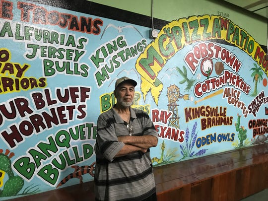 Artist Jessie Flores poses in front of the mural he painted at MG's Pizza in Robstown, which displays nearly every high school within 50 miles of Robstown on Tuesday, January 29, 2019.